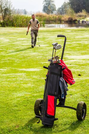 caddie: a golf player playing on a beautiful golf course and a golf bag full of golf clubs