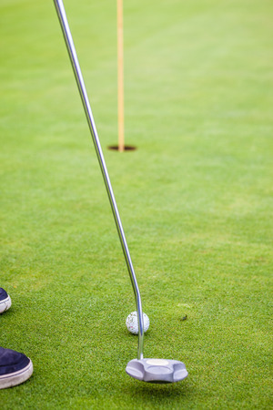 midlife: a golf player aiming for the hole on the green with a putter
