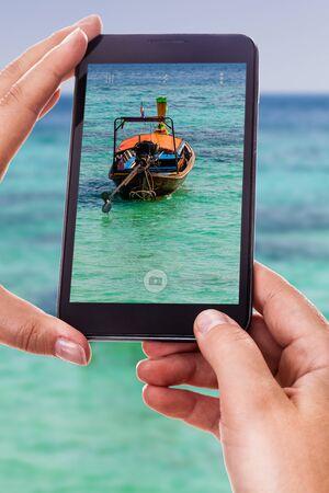 tail woman: una mujer que utiliza un tel�fono inteligente para tomar una foto de un tailand�s bote de cola larga tradicional flotando en un mar tropical Foto de archivo