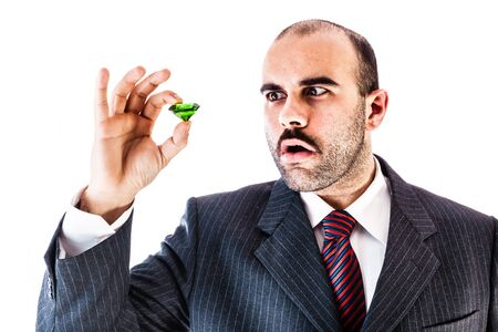 portrait of a classy businessman holding a big green emerald isolated over a white background