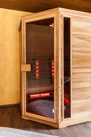 a small wooden infrarered sauna booth in a spa Stock Photo