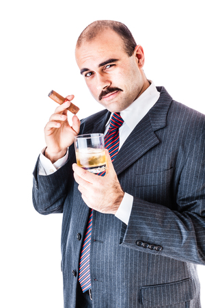 portrait of a classy businessman toasting with a glass of whiskey and smoking a cigar isolated over a white background