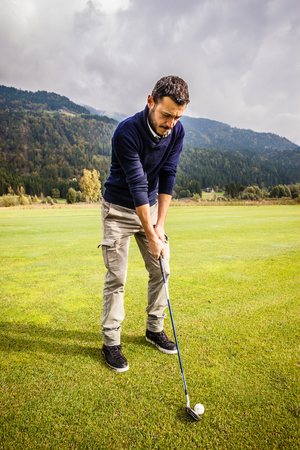 a golf player making a swing on a vibrant beautiful golf course Stock Photo