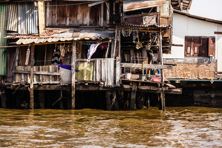 dwelling: Wooden slums on stilts on the riverside of Chao Praya River in Bangkok, Thailand Stock Photo