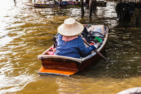 praya: a thai hawker with the typical hat floating with her boat on the Chao Praya River, Thailand