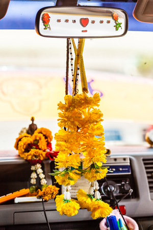 lucky charm: interior of a thai car with the typical marigold garland as a lucky charm Stock Photo