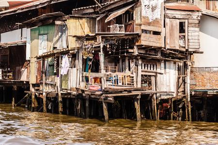 stilts: Wooden slums on stilts on the riverside of Chao Praya River in Bangkok, Thailand Stock Photo