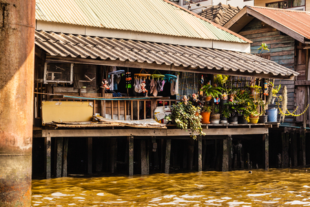 encroach: Wooden slums on stilts on the riverside of Chao Praya River in Bangkok, Thailand Stock Photo