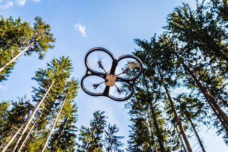 quad: a small spy quad copter scout drone flying through the trees in a forest Stock Photo