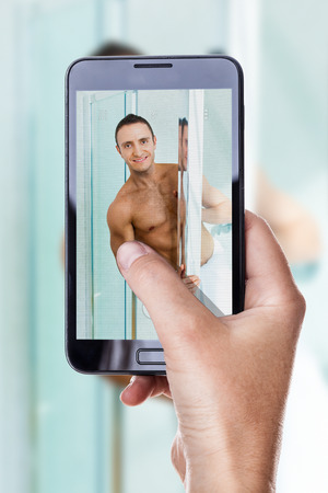 a woman using a smart phone to take a photo of a muscular man in the bathroom photo