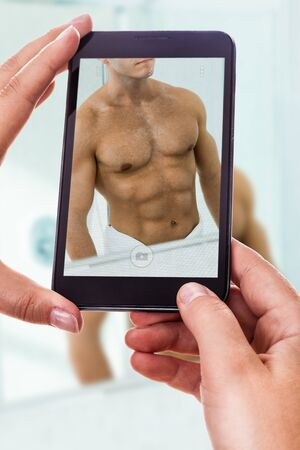 a woman using a smart phone to take a photo of the abdominals of a muscular man photo