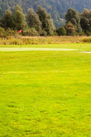 golf course: a golf hole with a flag pole in a beautiful golf course