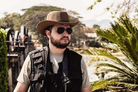 stetson: a photographer or adventurer with sunglasses and a stetson near the bridge on the river Kwai Stock Photo