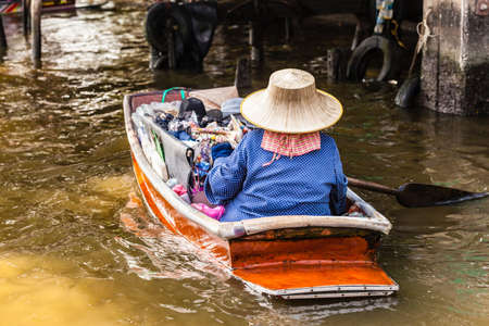 hawker: a thai hawker with the typical hat floating with her boat on the Chao Praya River, Thailand