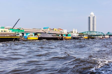 mining ships: a minerary barge full of gravel floating on the chao praya river in bangkok city