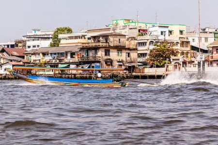 chao praya: a typical and colorful thai long tail boat speeding on the Chao Praya River in Bangkok City Stock Photo