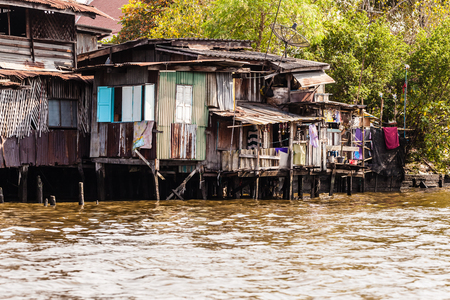 deprived: Wooden slums on stilts on the riverside of Chao Praya River in Bangkok, Thailand Stock Photo