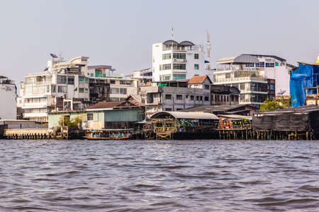 praya: Wooden slums on stilts on the riverside of Chao Praya River in Bangkok, Thailand Stock Photo