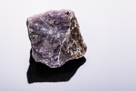 close up shot of a fragment of lepidolite mineral on a dark surface
