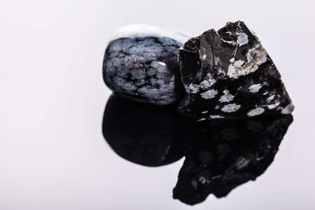 stoneage: close up shot of a fragment of obsidian mineral on a dark surface