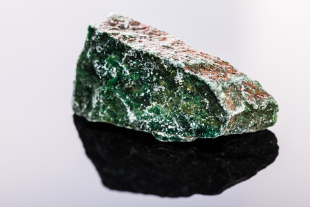 gemology: close up shot of a fragment of fuchsite mineral on a dark surface