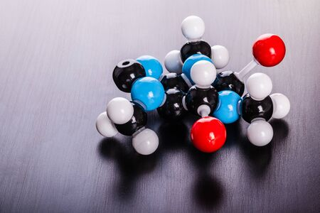 caffeine molecule: a caffeine chemical molecular structure model on a wooden surface Stock Photo