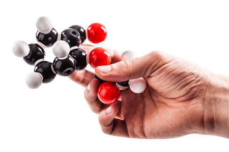 chemical structure: a male hand holding a molecule chemical structure model isolated over a white background