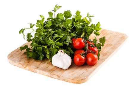 parsel: some cherry tomatoes, parsley and garlic on a cutting board isolated over a white background