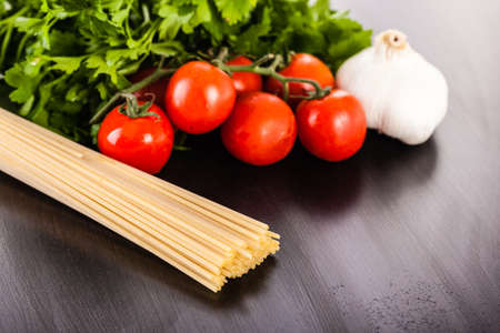 parsel: a bunch of spaghetti, some cherry tomatoes, parsley and garlic on a dark surface