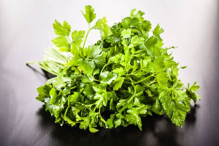 potherb: a heap of vibrant green parsley on a dark wooden surface Stock Photo