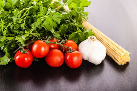 a bunch of spaghetti, some cherry tomatoes, parsley and garlic on a dark surface