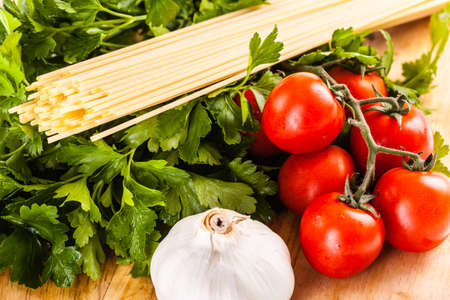 parsel: a bunch of spaghetti, some cherry tomatoes, parsley and garlic on a cutting board