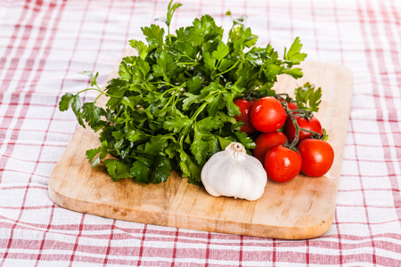 parsel: some cherry tomatoes, parsley and garlic on a cutting board isolated over a kitchen cloth
