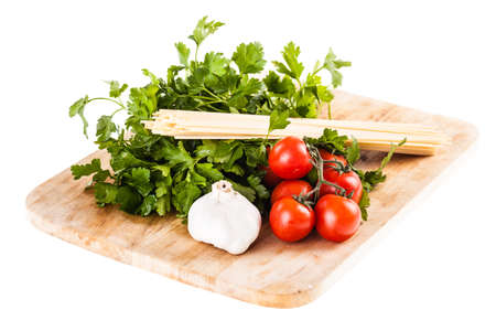 parsel: a bunch of spaghetti, some cherry tomatoes, parsley and garlic on a cutting board isolated over a white background Stock Photo