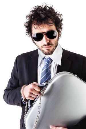 wrist cuffs: Businessman wearing a suit with a secure suitcase attached with handcuffs isolated over a white background