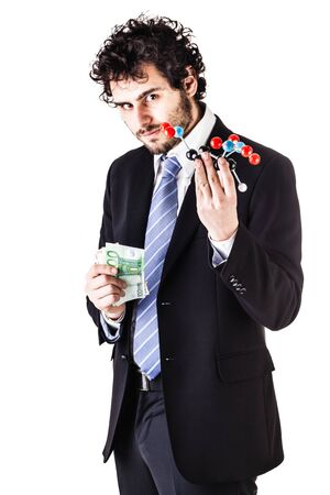 tnt: a businessman wearing a suit and a tie holding a trinitrotoluene tnt molecular model and money bills isolated over white Stock Photo