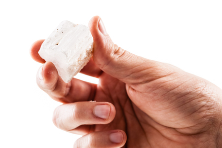 a male hand holding a fragment of selenite mineral isolated on a white background