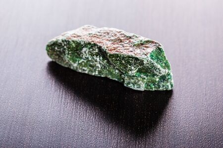 close up shot of a fragment of fuchsite mineral on a dark surface