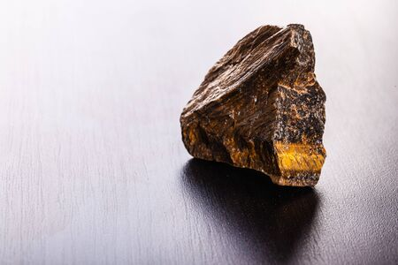 chatoyant: close up shot of a fragment of tigers eye mineral on a dark surface