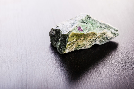 rare rocks: close up shot of a fragment of zoisite mineral on a dark surface Stock Photo