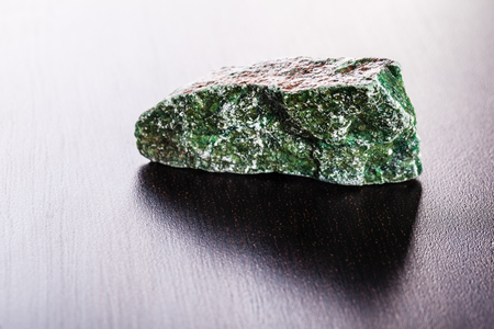 schist: close up shot of a fragment of fuchsite mineral on a dark surface