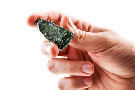 schist: a male hand holding a fragment of fuchsite mineral isolated on a white background