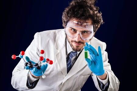 molecular model: a doctor or researcher with a white lab coat holding a trinitrotoluene tnt molecular model and a vial with green fluid