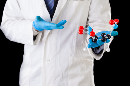tnt: a doctor or researcher with a white lab coat holding a trinitrotoluene tnt molecular model