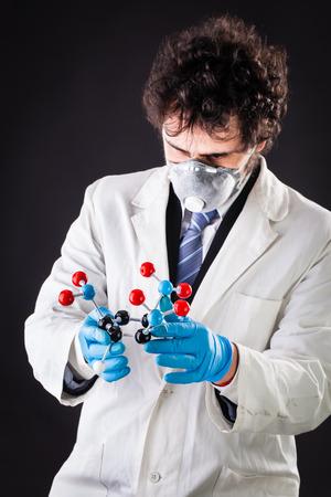 molecular model: a doctor or researcher with a white lab coat holding a trinitrotoluene tnt molecular model