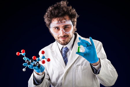 tnt: a doctor or researcher with a white lab coat holding a trinitrotoluene tnt molecular model and a vial with green fluid
