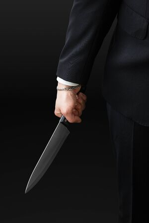 vindictive: an handsome businessman wearing a suit and a tie holding a big kitchen knife Stock Photo