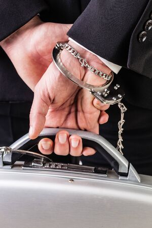 wrist cuffs: Businessman wearing a suit with a secure suitcase attached with handcuffs
