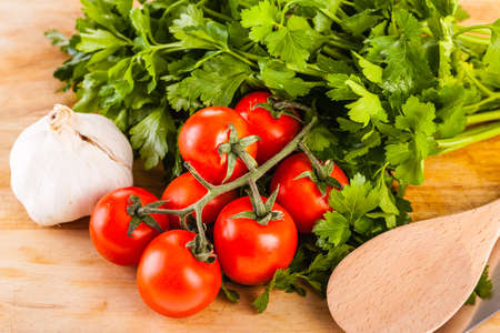parsel: some cherry tomatoes, parsley and garlic on a cutting board