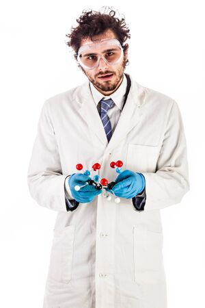 tnt: a doctor or researcher with a white lab coat holding a trinitrotoluene tnt molecular model isolated over white